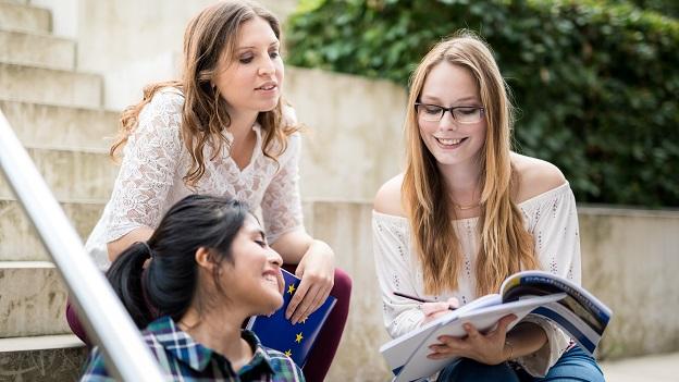 Drei Studentinnen auf Treppe beim Arbeiten