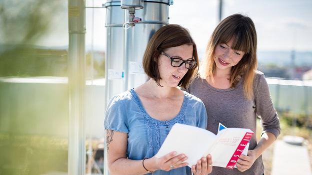 Zwei Studentinnen schauen in ein Buch.