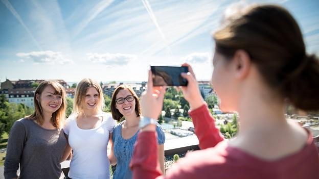 Foto von 3 Studierenden über den Dächern der Stadt
