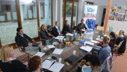 Vereinsmitglieder um einen Tisch beim Arbeiten.