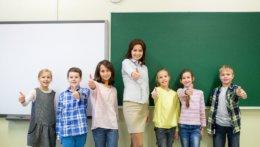 Lehrerin und ihre Schüler halten Daumen hoch und lachen