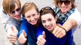 4 junge Menschen lachen und zeigen Daumen hoch