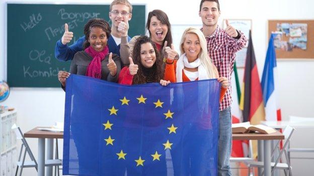 6 internationale Studierende stehen in einem Klassenzimmer, zeigen ihre Daumen hoch und halten eine Europa-Flagge