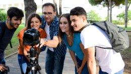 Ein Lehrer und 4 Schüler stehen vor einer Kamera und drehen einen Film.
