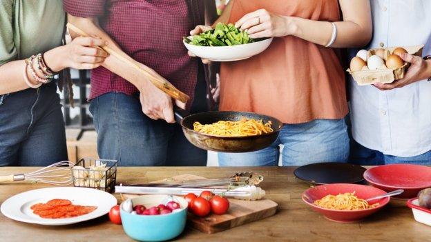 4 Personen beim Kochen von Pasta. Auf dem Tisch davor stehen die Zutaten.