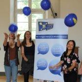 Das Standort-Team wirft Luftballons in die Luft, in der Mitte steht ein Roll-Up.