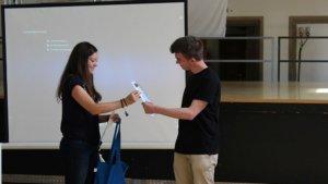 Standortkoordinatorin gibt einem Gaststudierenden sein Teilnahmezertifikat.