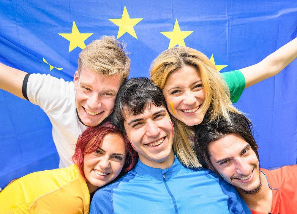 Fünf Europäerinnen und Europäer halten gemeinsam eine Europaflagge hinter ihren Rücken und sind fröhlich.