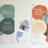 Foto der zwei neuen Plakate und der Postkarte.
