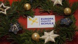 EmS-Logo liegt auf einem weihnachtlichen Teller mit Tannenzweigen und Weihnachtsdekoration.