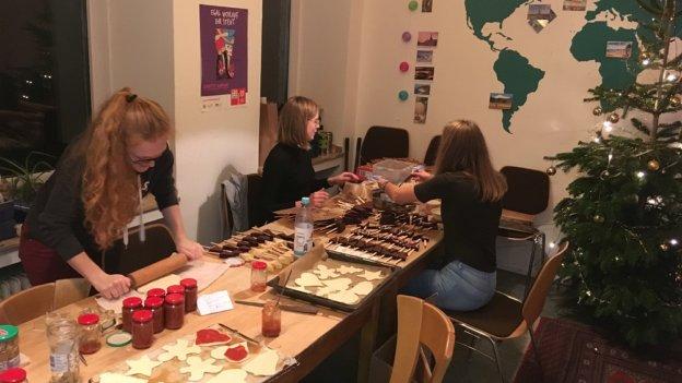 3 junge Frauen backen Pizza und Plätzchen.
