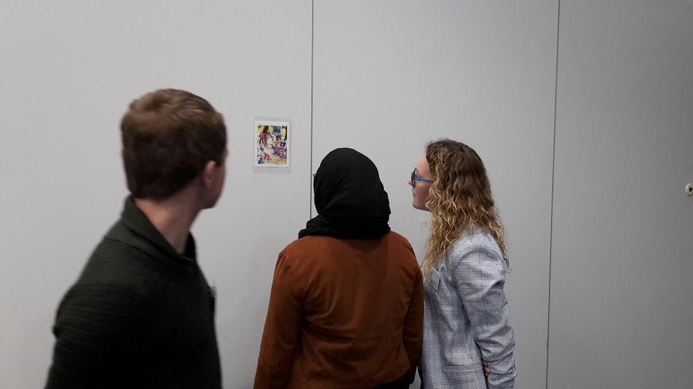 3 Teilnehmende betrachten ein Bild, das an der Wand hängt.