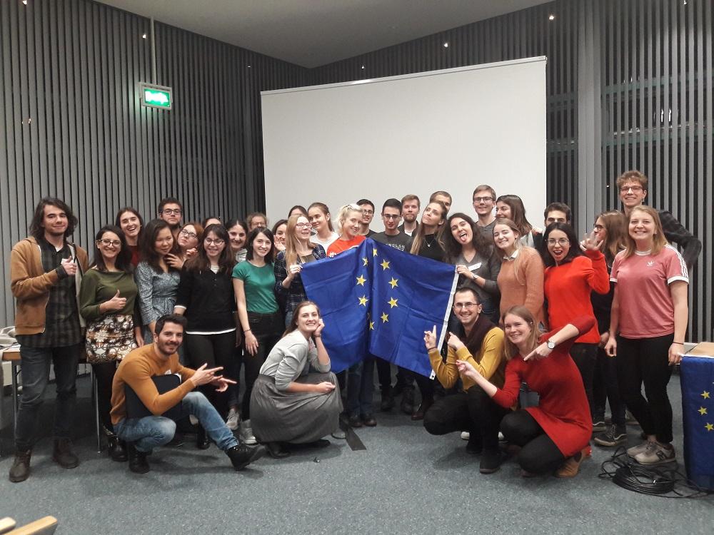 Gruppenfoto aller Teilnehmenden, die fröhlich schauen und auf eine Europaflagge deuten.