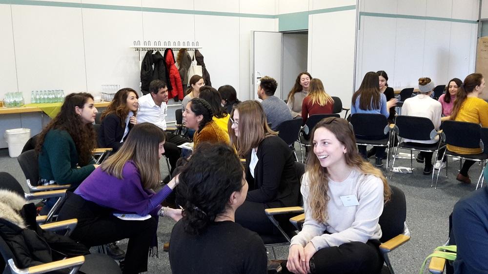 Teilnehmende sitzen in einem inneren und äußeren Stuhlkreis und diskutieren jeweils zu zweit.
