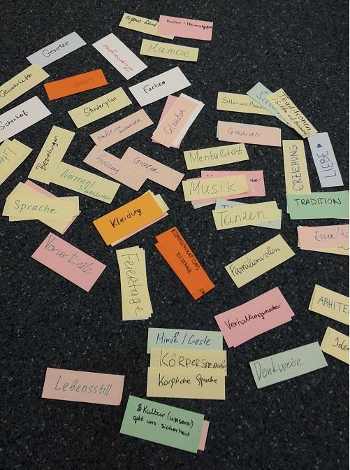 Viele Kärtchen mit Worten zum Thema Kultur liegen verteilt auf dem Boden.