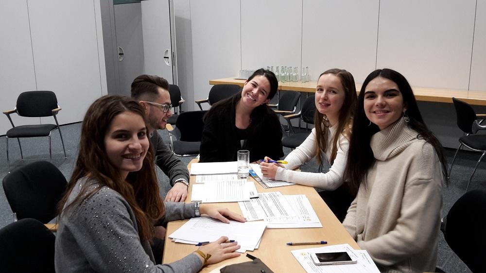 5 Teilnehmende sitzen um einen Tisch, auf dem Zeitplanungsblätter liegen. Sie lachen in die Kamera.