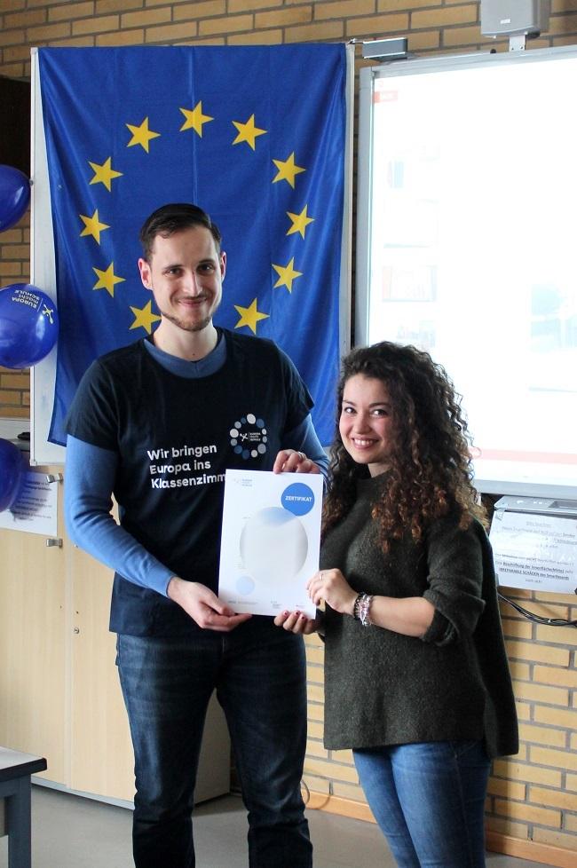Standortkoordinator übergibt Gaststudentin ihr Teilnahmezertifikat