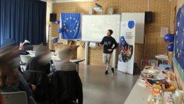 Gaststudent präsentiert sein Projekt vor einigen Schülern. Alle befinden sich in einem Klassenzimmer, am Rand stehen Snacks und Getränke.