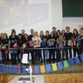 Europäische Gaststudierende und Standort-Team stehen gemeinsam auf der Bühne und halten eine Kette mit europäischen Flaggen.