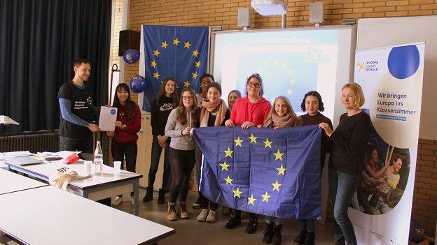 Einige Schülerinnen und Schüler der Klasse sowie die Lehrerin und ein Standortmitglied stehen vorne in einem Klassenzimmer, halten eine Europaflagge und lachen in die Kamera.