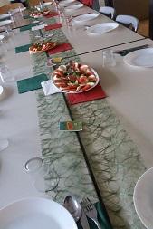 Ein gedeckter Tisch, in der Mitte stehen Platten mit Tomate- Mozzarella.