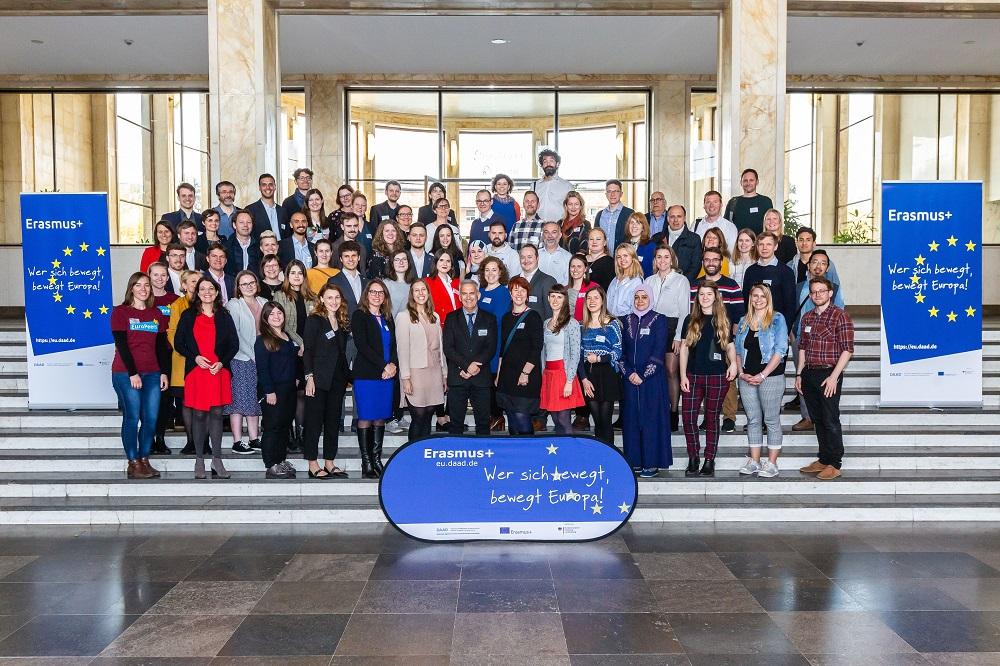 Gruppenfoto aller Teilnehmenden, die auf einer Treppe stehen. Daneben stehen zwei Erasmus Rollbanner.