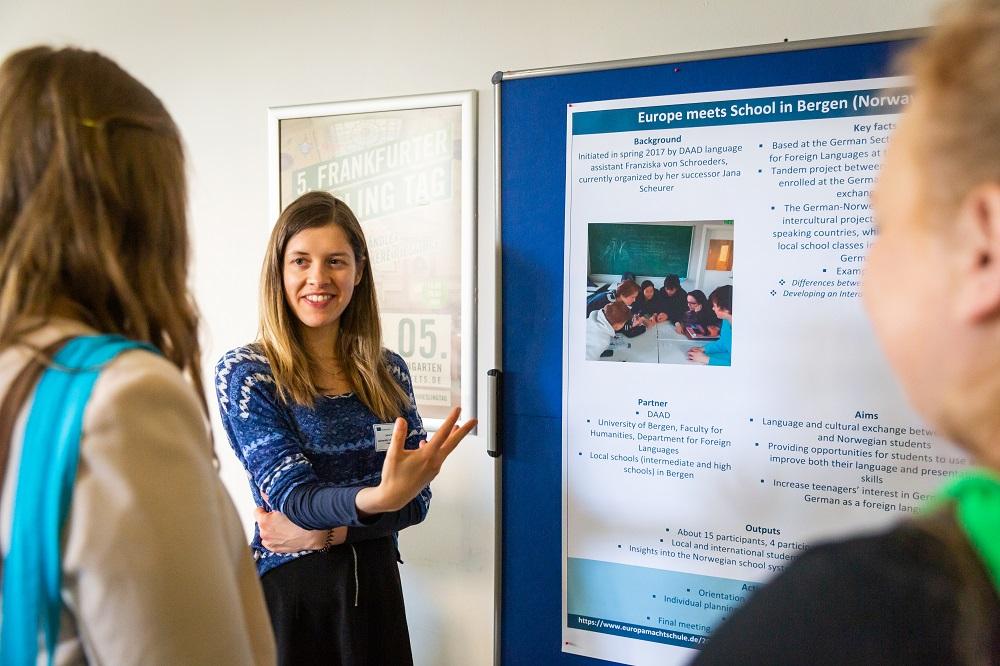 Jana Scheurer steht vor ihrem Plakat an der Wand und erklärt zwei Personen etwas.
