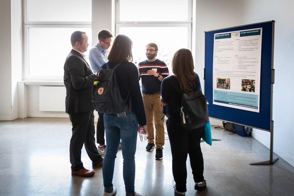Frank Wittmann und Robert Gieske erklären drei Personen Europa macht Schule. Alle stehen vor einer Pinnwand, auf der ein Plakat hängt.