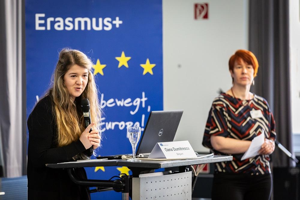 Oana Dumitrescu steht vor einem Pult mit Laptop, im Hintergrund sind Beate Körner und ein Rollbanner zu sehen.