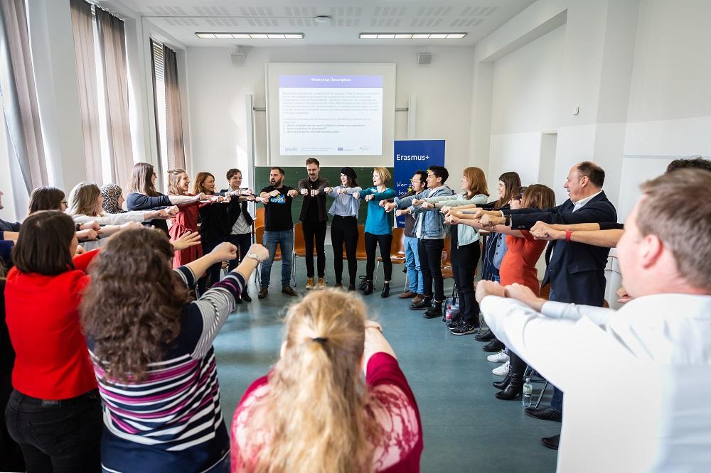 Mehrere Personen bilden einen Kreis und halten ihre Hände hoch.