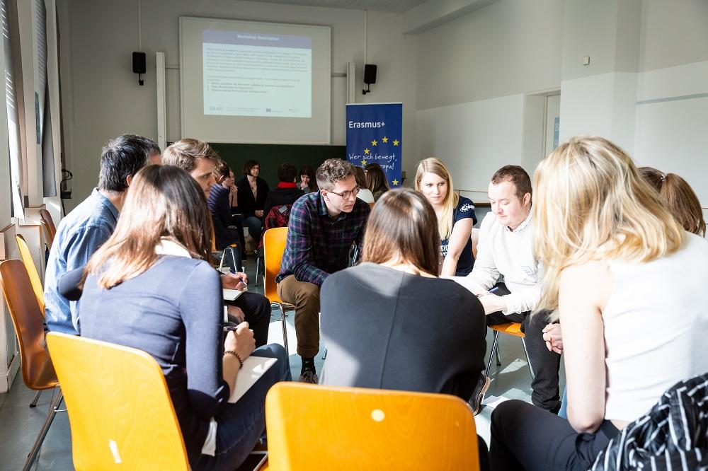 Im Vordergrund ist ein Stuhlkreis, mehrere Personen diskutieren. Im Hintergrund ist ein weiterer Stuhlkreis zu sehen.