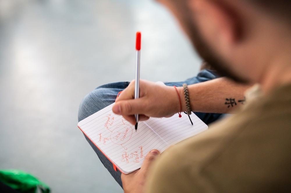 Eine schreibende Hand notiert in einem Notizbuch Ideen.