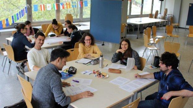 Studierende sitzen in einem Raum an zwei Gruppentischen, auf denen Tischen liegen Dokumente und Stifte.
