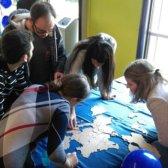 5 Studierende beugen sich über einen Tisch, auf dem ein Europa-Puzzle liegt.