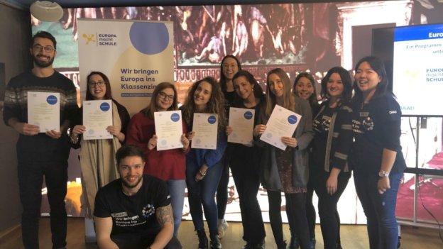 Die Mitglieder des Standort-Teams und die Gaststudierenden, die ihre Zertifikate in der Hand halten, lächeln in die Kamera. Im Hintergrund steht ein EmS-Banner.