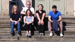 Die Mitglieder der AG Auslandsstandorte sitzen auf einer Treppen außen und lachen in die Kamera.