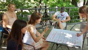Draußen liegt auf einem Tisch ein großes Papier, auf dem die herumstehenden und -sitzenden Personen ihre Ideen notieren.