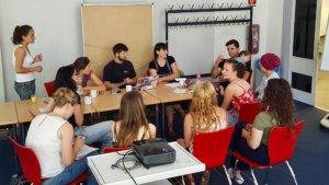 Mehrere Leute sitzen um Tische herum und diskutieren ihre Ideen.
