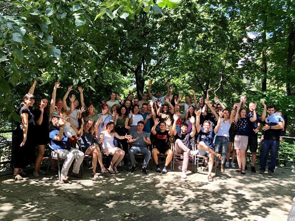 Gruppenfoto aller Teilnehmenden des Jahrestreffens, die fröhlich in die Kamera lachen und ihre Arme bewegen.