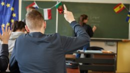 Ein Schüler meldet sich, eine Gaststudierende steht an der Tafel, im Hintergrund ist die Europaflagge und weitere Flaggen zu sehen.