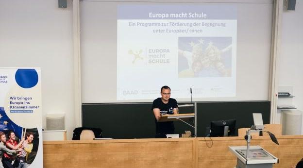 Hermann Jakobi steht vorne in einem Hörsaal am Rednerpult. Im Hintergrund ist eine EmS-Präsnetation und ein EmS-Roll-Up zu sehen