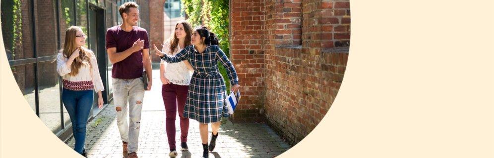 3 Studentinnen und ein Student laufen in einem Innenhof auf die Kamera zu. Sie scherzen miteinander. von Allwörden/DAAD