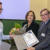 Herr Wölfle vom Standort Heidelberg erhält Blumen und Zertifikat von Frau Wintermantel und Herr Kraus. Alle lachen in die Kamera.