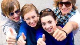 4 junge Studierende lachen in die Kamera und halten ihren Dauemn hoch