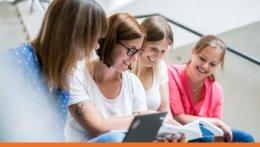 4 Studentinnen sitzen auf einer Treppe und arbeiten gemeinsam mit einem Laptop und einer Broschüre.