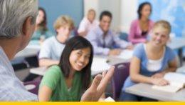 Ein Lehrer steht vor einer Klasse, die Schüler schauen interessiert.