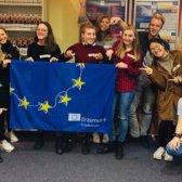 12 junge Erwachsene halten eine Europaflagge lächelnd in die Kamera