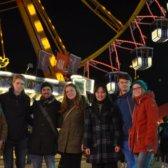 7 junge Menschen stehen vor einem Riesenrad auf dem Hamburger DOM
