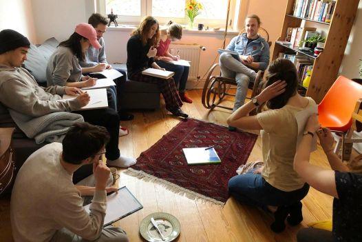 9 junge Menschen sitzen in einem Raum verteilt und schreiben etwas auf ein Baltt Papier, welches auf ihrem Schoß liegt