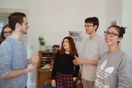 Man sieht 5 junge Menschen in einem Raum, die etwas besprechen.
